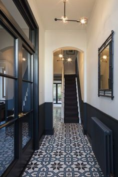 An inky, dark blue wainscot, cream walls, and interesting tile.