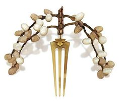 """Horn, Mother-Of-Pearl, Enamel and Topaz Tiara comb, Circa 1903, Rene Lalique.""""   Designed as branches of pussy willows, the trunk bark defined by wedge-shaped topaz offset by a brown enamel field, continuing to carved gold and horn branches painted with brown enamelling, punctuated with carved mother-of-pearl and horn pussy willows in various stages of bloom, the three-prolonged comb of horn, connected to the diadem by a gold hinge.  Signed"""