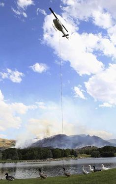A helicopter gets water from a pond to drop on the Rose Crest fire as ducks walk by in Herriman, Utah, June 29, 2012.