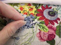 The needlepoint embroiderer stitches the floral pattern first, and then stitches the background. Here the background is the white canvas tha...