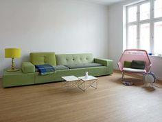 Rene hvite vegger og åpne vinduer skaper en enkel base for interiøret. Eierne har derfor valgt å innrede med friske farger, en lav sofa i grønn, en limegrønn lampe, og en rosa stol.