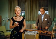"""1955. """"Peggy Lee singing into tape recorder accompanied by Sonny Burke. Soundtrack for Walt Disney CinemaScope cartoon feature Lady and the Tramp."""""""