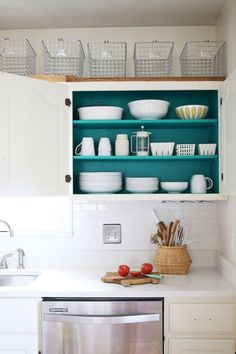 Adding a color pop in the kitchen! teal inside the cabinets with all white dishes = perfection.
