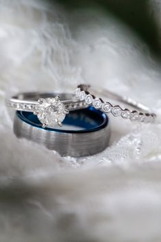 This engagement ring with a round cut diamond center is a classic and timeless ring. We love the wedding band the bride chose to accompany her engagement ring. The little round diamonds give a modern touch to this thin wedding band. The mens wedding band has a classic silver finish with a fun pop of color with a blue trim. The delicate lace wedding dress is perfect background to make the rings pop!
