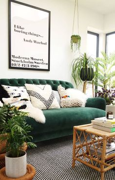 Green Velvet Sofa styled in monochrome family home by The Only Girl in the House with lots of house plants, hanging plants, string of pearls plant and ponytail palm in basket. Black and white rug and cowhide. Andy Warhol quote print, I like boring things. how to style a velvet sofa from DFS Bailey Sofa and sofa workshop. Wicker table and woven cushions