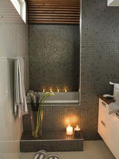 Dark mosaic tile on the entrance to a half-hidden bathtub.