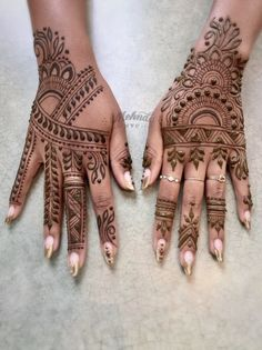 Hands with flowing dense floral mehndi designs.