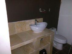 Pared color chocolate, mueble color marfil de mármol y piso enchape marrón.