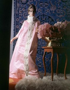 1963 Astrid Heeren in tea coat of pink, silk-faced satin, edged in sequins, brilliants, and beads by Perfect, worn here with white mink collar, photo by Horst, Vogue,