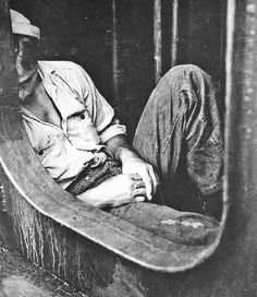 Sailor sleeping just inside a hatch on board the battleship New Jersey while en route to the Philippines in December 1944.