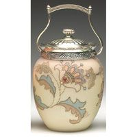 "Mt. Washington Crown Milano biscuit jar, ivory satin glass with enameled stylized flowers and leaves in brown blue and white with raised beading, metal rim, lid and handle, 5.5""w x 7.5""h $300 - $400"