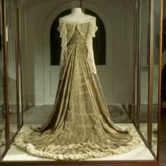 """The Peacock Dress, made by the House of Worth,. was worn by Mary, Lady Curzon, Vicereine of India, at the Delhi Durbar which was held in 1903 in celebration of the coronation of Edward VII. A guest at the ball remarked: """"You cannot conceive what a dream she looked"""".The material, worked by men in India, is shining cloth of gold with a pattern of overlapping peacock feathers in gold and silk thread on a silk chiffon background."""