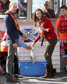 Catherine, Duchess of Cambridge, holds up a fish as Prince William, Duke of Cambridge looks on as they head out on a fishing trip with Skidegate youth centre children during the Royal Tour of Canada on Sept. 30, 2016.