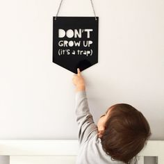 Black nursery sign, Dont grow up its a trap, made of 3mm black acrylic. The dimensions of this kids wall decor are 20cm x 25cm at its widest points.