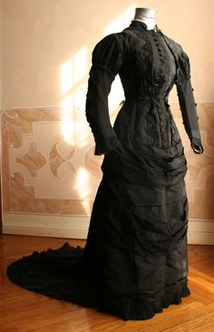 1876 front - Full dress will probably be in mourning taffetas black closed in front by a series of buttons and decorated in the center of the back by a band of black lace, terminating in a bow. Within a few strips of the skirt loops of metal rings allow the train to curl up to make it disappear. ____ (translated from Italian by Google)