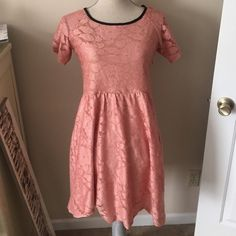 Pink Lace Dress Pink lace dress with black seam around the neck. Zips up the side. Has a beige liner, so it is not see through. Small stain on the inside of the liner on the right side. Not noticeable from the outside (see pic 3). Size L by Ezra. Ezra Dresses