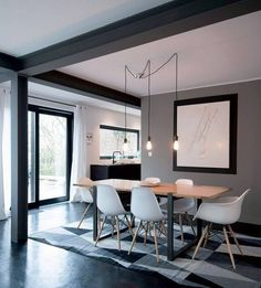 Grey dining space with Eames chairs and industrial pendants