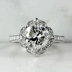 14k white gold scalloped halo engagement ring with milgrain detail. 30 diamonds, 0.32 CTW.