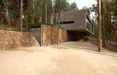 house in Chile surrounded by forest. Love the stone wall and the simplicity of design. For more details.    http://freshome.com/2013/04/19/original-playful-layout-showcased-by-omnibus-house-in-chile/design-omnibus-house/