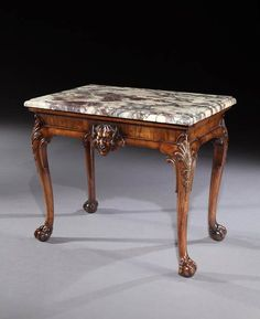 A mid 18th century carved walnut side table attributed to Giles Grendey, having an 18th century replaced brèche violette marble top above a cross veneered concave frieze applied with a central satyr mask; on cabriole legs with crisply carved anthemion to the knees with husks below, terminating in claw and ball feet.