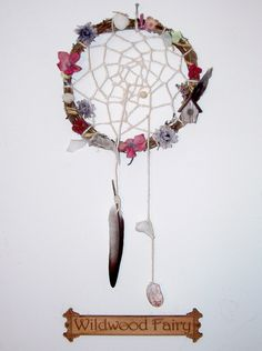My first dream catcher. I call this New Home Love - features repurposed wreath and flowers. The little house is from an outdoor arrangement. Shells are from Virginia Beach.