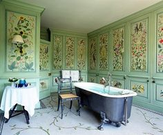 A bath in the England home of Sting and Trudie styler features  painted botanical panels, an antique steel tub, and a mosaic floor.