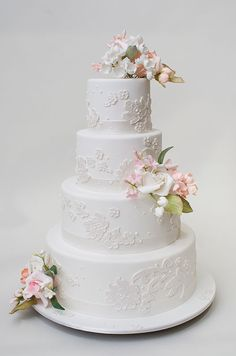 This romantic white cake features pink and white sugar flowers- a fabulous option for a spring wedding.