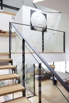 Photo DT127 - ESCA'DROIT® 2 Quartiers Tournants avec Grand Palier Intermédiaire Rectangulaire. Escalier d'intérieur design en métal, bois et verre pour un intérieur contemporain type loft. Limons découpés en crémaillères en 'L'. Rampe et garde-corps composés d'une main courante, de montants en fer plat graphique et de panneaux verre feuilleté clair pour la transparence et la modernité. Finition : acier brut patiné. - © Photo : Nicolas GRANDMAISON