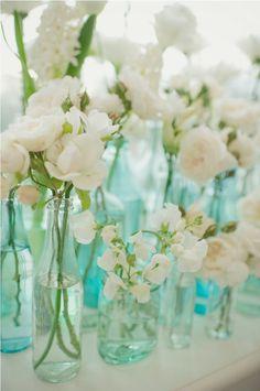white flowers in seafoam blue bottles