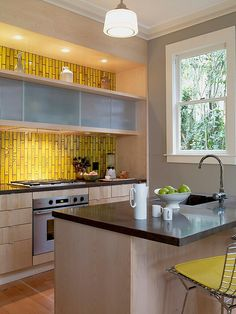 Bright kitchen splashback, and I love the position of the kitchen cabinets, and the spotlighting that illuminates the vases