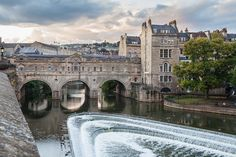 Pulteney Bridge is an arch bridge that crosses the River Avon in Bath, England. Designed by Robert Adam and completed by it connects Bath with the Georgian town of Bathwick. The Grade I listed building has shops built across its full ft) span. Best Hotels In Bath, Most Beautiful Cities, Beautiful Places To Visit, Bristol, Avon, Castles To Visit, Places In England, London Bridge, England