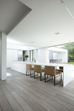 Dining table extending off kitchen island. Woning M/P - Architectenburo Govaert & Vanhoutte