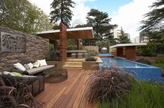 lots to like: stone wall with metal art, mosaic tiled pool, decorative grasses and covered outdoor dining | Rolling Stone Landscaping, Melbourne international flower and garden show 2007