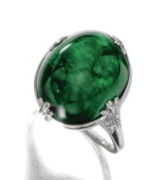 EMERALD AND DIAMOND RING, CIRCA 1935.  The cabochon emerald weighing approximately 16.50 carats, within an openwork setting decorated with single-cut and round diamonds, mounted in platinum