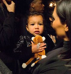 """Kim Kardashian and North West. Unfortunately, the little girl got upset before the show and was photographed crying in her mom's lap. A source explained the incident to Us at the time, saying, """"North had a moment for one second when she saw a photographer on the other side of the runway with a toy monkey that looked exactly like her favorite one at home."""