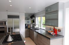 This Modern Kitchen has a mixture of Italian Laminate, High Gloss White Paint, Smoked Glass Doors and floating shelves.