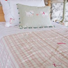 Susie Watson Designs -  Susie Watson Designs Fabric Collection - Candy-striped pink bedcover with beribboned white dogs; similar patterned cushions with  pale green and white backgrounds.