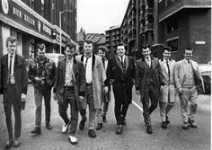 Teddy Boys (originally known as Cosh Boys) were the original teen rebels, influenced by US' rock 'n' roll with  a distinctive style taken from the Edwardian era. The style consisted of a long, dark drape jacket with velvet trim (hanging from the shoulders); tight, drainpipe trousers, worn short to expose brightly coloured socks; crepe-soled shoes & bootlace tie. Hair was usually heavily greased. They were blamed for society's ills in the 1950s due to reputation for gang-led culture…