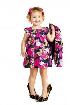 Beautiful little girl in high-heeled shoes over white background Stock Photo