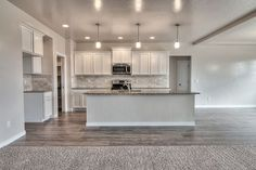 Huge kitchen with Merillat - Spring Valley, Maple, Cotton Cabinets, wood corbels under the raised breakfast bar, Woodland Maple wood laminate flooring, and Ashen White slab granite with an ea - Google Search