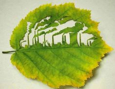 Fabbriche e ciminiere intagliate in una foglia verde.  -  Factories and chimneys carved in a green leaf.