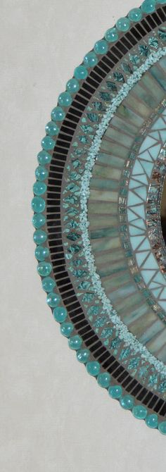 This mosaic was created using stained glass in shades of aqua along with black, aqua/champagne Van Gogh glass, crushed glass, turquoise beads, glass gems, and vitreous glass. It measures 24 across with with a 12 mirror. The hanging hardware is attached and its ready to be hung.