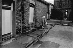 Magnum Photos - Ian Berry G. An old women trudges past boarded up terraced houses with a statue of Christ beyond. Ian Berry, Three Gorges Dam, Great Wide Open, Louisiana Purchase, Akashic Records, Photographer Portfolio, Old London, Magnum Photos, Sunderland