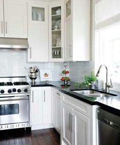 I'm keeping this one. Black countertops, white cabinets, long silver hardware, stainless appliances, white subway tile.