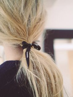 Blonde ponytail tied with black Chanel ribbon.