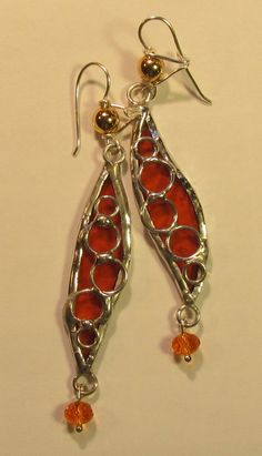 Free form glass earrings in brilliant orange and soldered with Silvergleem.   Unique clasp hooks.  $20