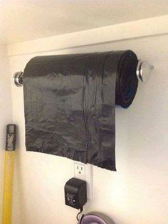 Use a paper towel holder in your garage to hold garbage bag rolls