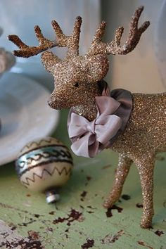 DIY Glittered Reindeer: Use a paintbrush & coat Dollar Store animals in white glue. Spoon glitter onto deer; gently shake excess into bowl. Let dry. Touch up any bare spots & add bow.
