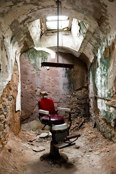 An eerie photo taken on Oct. shows a lone chair in a barber shop in cellblock 10 at Eastern State Penitentiary in Philadelphia. The penitentiary took in its first inmate in closed in 1971 and reopened as a museum in Abandoned Buildings, Abandoned Places, Places Around The World, Around The Worlds, Urban Decay Photography, Eastern State Penitentiary, Chair Photography, World Photo, Cool House Designs