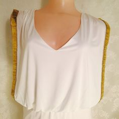 Amazing white and gold blouse. Amazing white and gold blouse. 94% polyester 6% Spandex. Lining is 100% Polyester. Beautiful accent gold on sleeves. Very unique! Adjustable string on back side. Love Reign Tops Blouses